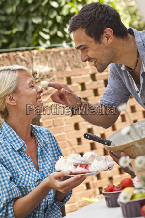 young couple fooling around with meringue