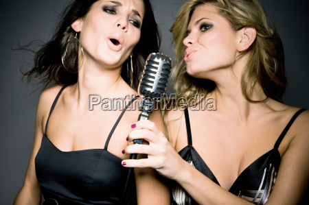 two women singing into mic