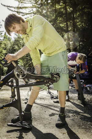 young couple fixing mountain bikes soquel