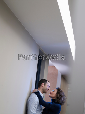 couple embracing in an office corridor