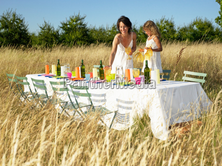mother and daughter setting the table