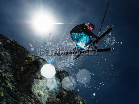 female skier jumping over rock