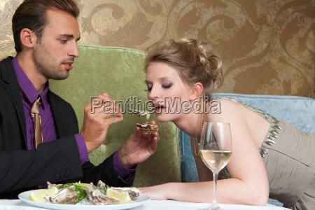 man feeding girlfriend oysters