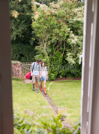 couple walking along path towards house