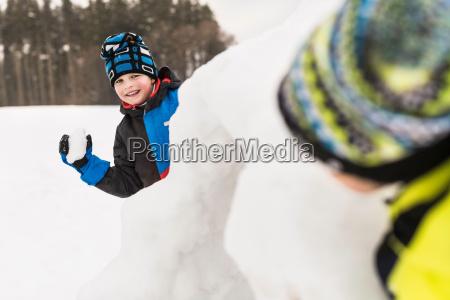 two boys having snowball fight