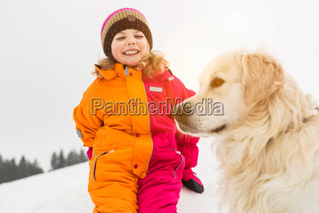 girl wearing winter clothing with dog