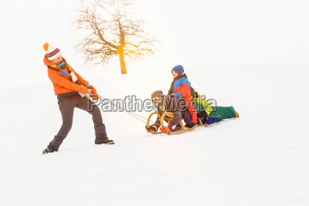 woman pulling toboggan in snow with