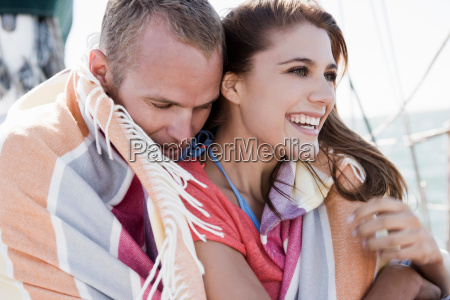 young couple on yacht wrapped in