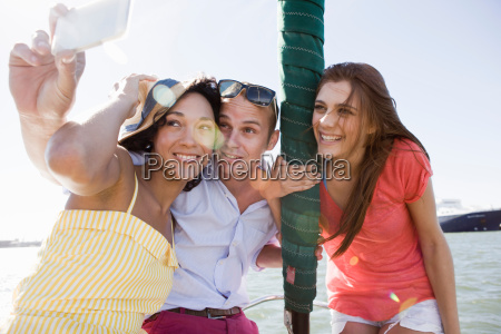 three young friends on yacht photographing