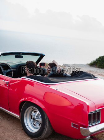 couple sitting in open topped car