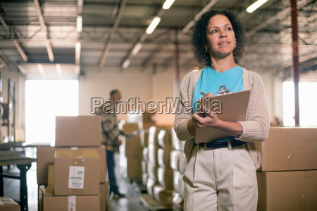 female warehouse worker holding clipboard