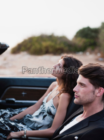 couple sitting in front of car