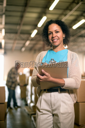 portrait of female warehouse worker holding
