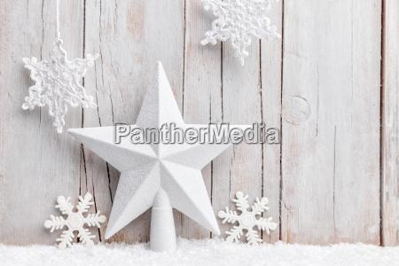 weihnachtsstern und schneeflocken mit schnee