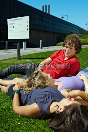 three young students relaxing on grass