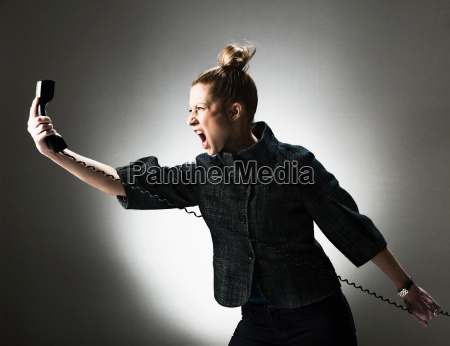 businesswoman shouting at telephone
