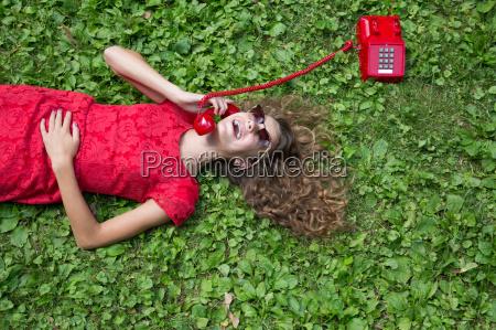 teenage girl lying on grass holding