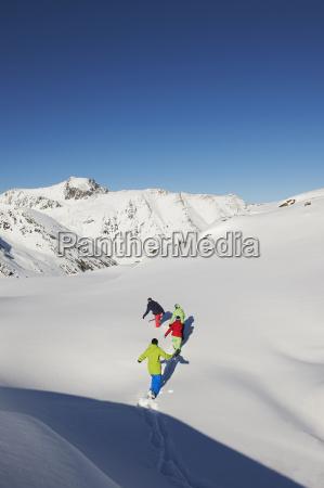 friends walking through snow kuhtai austria