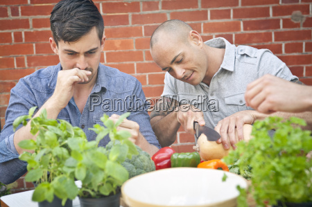 male friends preparing food with herbs