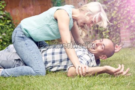 happy couple play fighting in garden