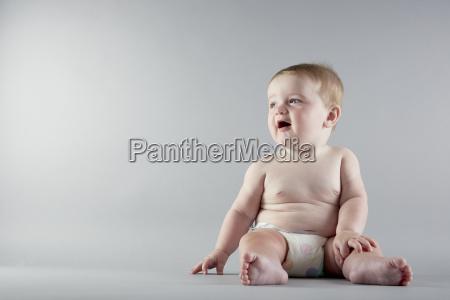 studio portrait of baby girl sitting