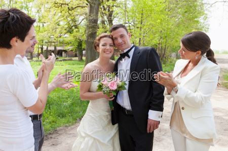 friends applauding newlywed couple