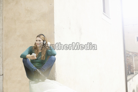 young woman sitting cross legged listening