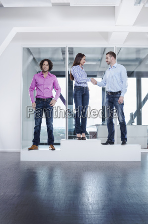 woman shaking hands with male colleague