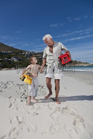 man holding grandsons hand on beach