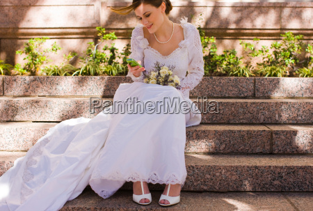 bride checking mobile phone at wedding
