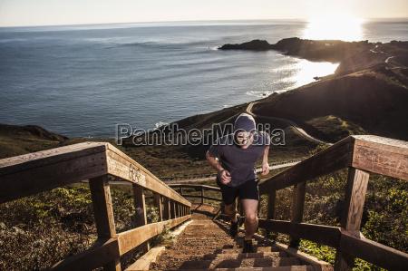young man running up coastal staircase