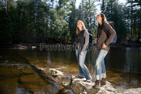 two women hiking beside lake