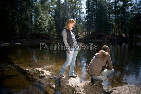 two women standing beside lake