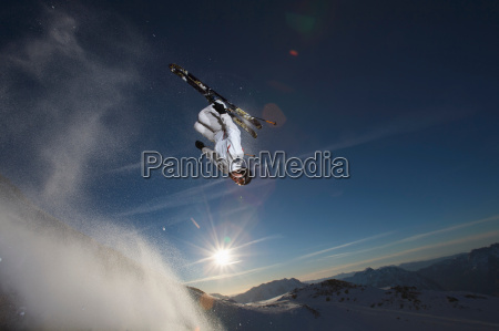 skier back flipping off a rock