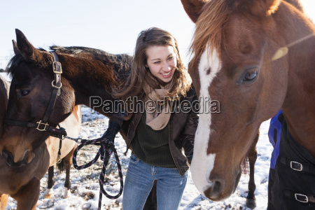 young woman with horses in winter