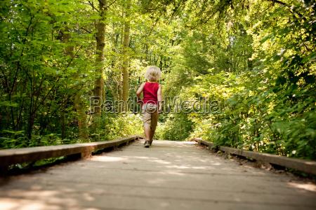 young boy walking along wooden walkway