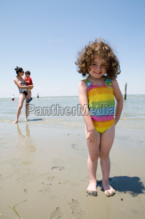 young girl standing on beach