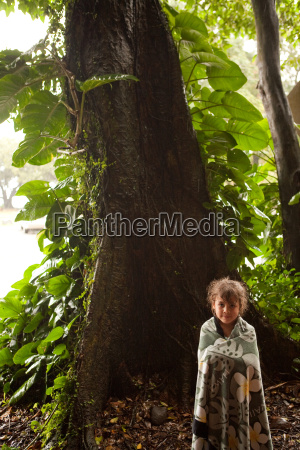 young girl standing by tree