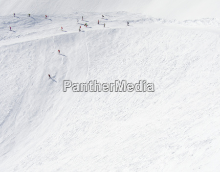 skiers going down steep mountain side