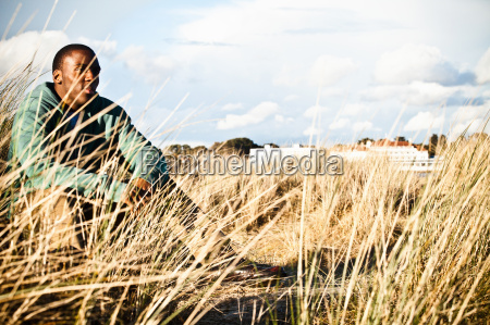 young man sitting in sand dunes