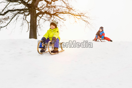 two boys on toboggans in snow