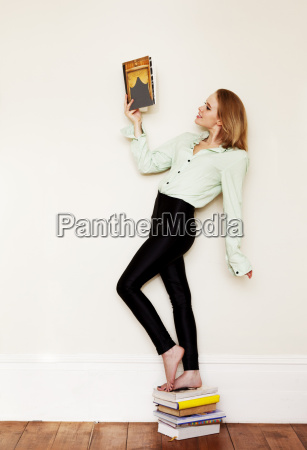 young woman standing on pile of