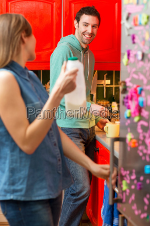 young couple in kitchen woman fetching