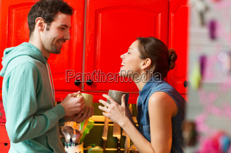 young couple in kitchen with coffee