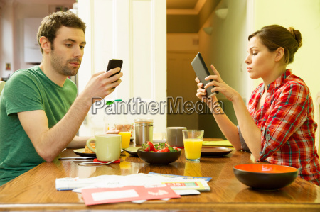 man using smartphone and woman using
