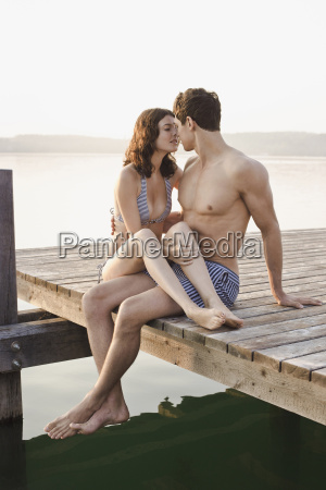 young couple sitting on lake pier