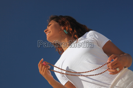 young woman holding beads on beach