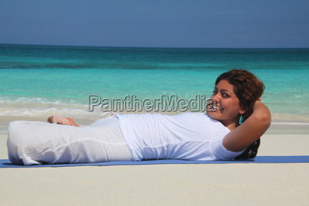 young woman on beach practicing yoga