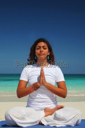 young woman doing yoga lotus position