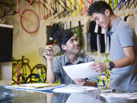 two young men with paperwork in